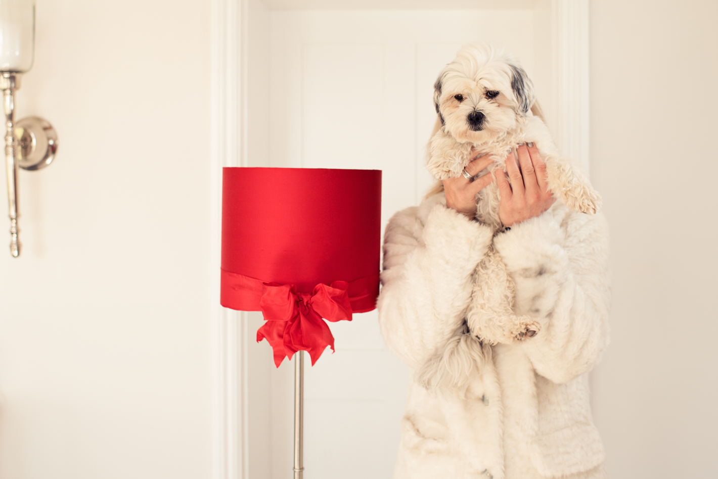 Humorous photo of a woman in a white fluffy coat, standing in a white room, next to a bright red lampshade, whilst holding a small, fluffy white dog in front of her face.